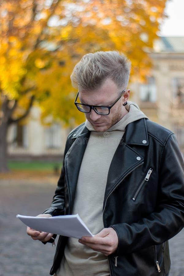 Ένας έξυπνος στοχαστικός τύπος στα περιστασιακά ενδύματα εξετάζει τα έγγραφα στο χέρι του στοκ φωτογραφία με δικαίωμα ελεύθερης χρήσης