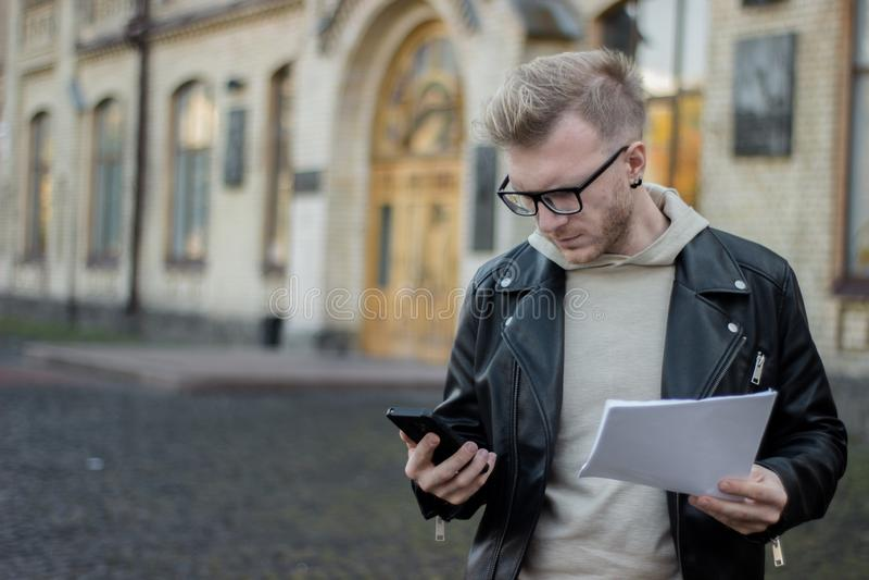 Ένας έξυπνος τύπος στα περιστασιακά ενδύματα κρατά τα έγγραφα και εξετάζει το τηλέφωνο στεμένος δίπλα στο πανεπιστήμιο στοκ εικόνα