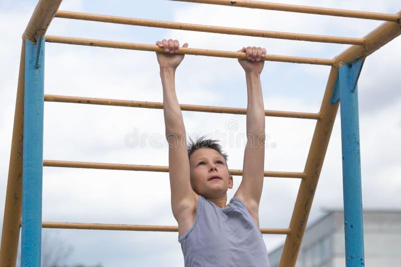 Ένας έφηβος σε μια μπλούζα συμμετέχει στη γυμναστική σε έναν οριζόντιο φραγμό στοκ εικόνα με δικαίωμα ελεύθερης χρήσης