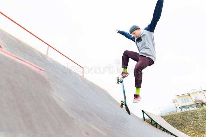 Ένας έφηβος skateboarder σε ένα καπέλο κάνει ένα τέχνασμα με ένα άλμα στην κεκλιμένη ράμπα Ένα skateboarder πετά στον αέρα στοκ φωτογραφία με δικαίωμα ελεύθερης χρήσης