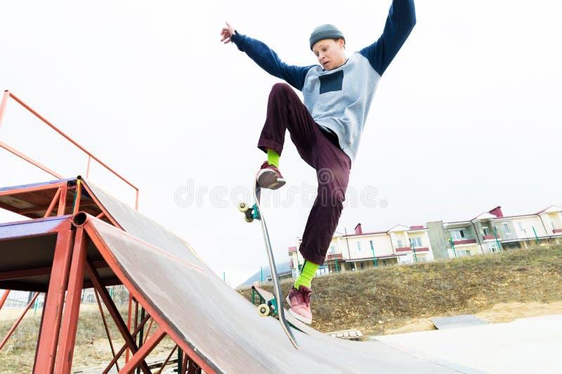 Ένας έφηβος skateboarder σε ένα καπέλο κάνει ένα τέχνασμα με ένα άλμα στην κεκλιμένη ράμπα Ένα skateboarder πετά στον αέρα στοκ εικόνες