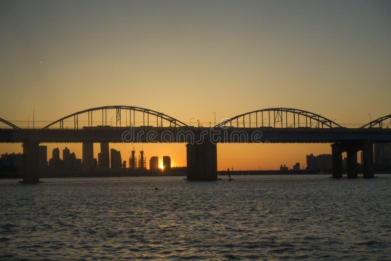Ένας ήρεμος ποταμός και μια αψίδα γεφυρώνουν και ηλιοβασίλεμα στο πάρκο Hangang, Σεούλ, Νότια Κορέα στοκ εικόνα