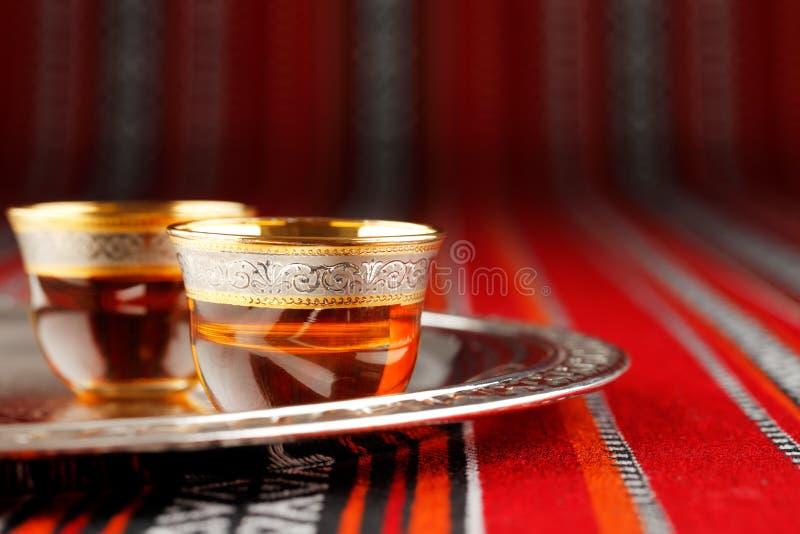 Ένας δίσκος των αραβικών κυπέλλων τσαγιού τοποθετείται στο αραβικό υφαμένο ύφασμα στοκ φωτογραφία