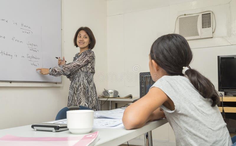 Ένας αγγλικός θηλυκός δάσκαλος γράφει και εξηγεί τους κανόνες των αγγλικών στο λευκό πίνακα, που διδάσκει ένα κορίτσι στοκ φωτογραφία με δικαίωμα ελεύθερης χρήσης