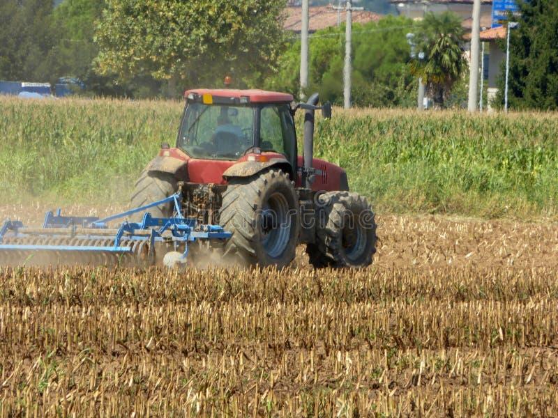 Ένας αγρότης με ένα τρακτέρ που οργώνει το έδαφος πρίν σπέρνει στο Lo στοκ εικόνες