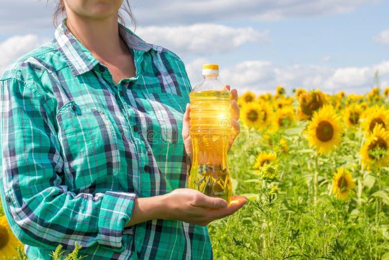 Ένας αγρότης που κρατά ένα μπουκάλι του φυτικού ελαίου στοκ φωτογραφία