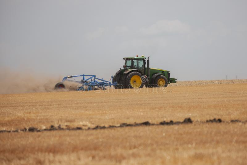 Ένας αγρότης σε ένα τρακτέρ προετοιμάζει το έδαφος με έναν καλλιεργητή ως τμήμα των pre-sowing δραστηριοτήτων στην αρχή της εποχή στοκ εικόνες
