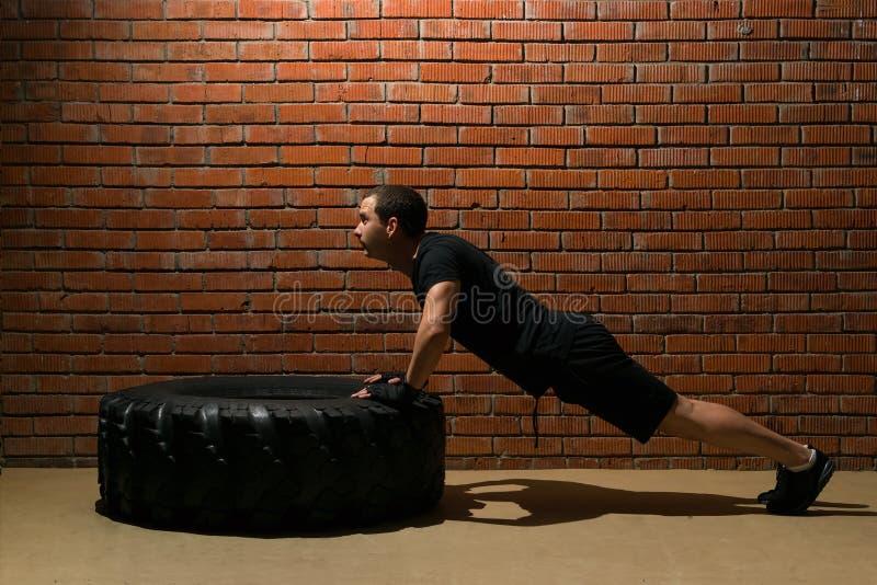 Ένας αθλητής συμπιέζει τη στήριξη στη ρόδα στη γυμναστική σε ένα υπόβαθρο τουβλότοιχος στοκ εικόνα