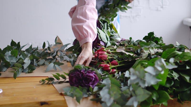 Ένας ανθοκόμος γυναικών βάζει τα λουλούδια στον εργασιακό χώρο της στοκ φωτογραφία