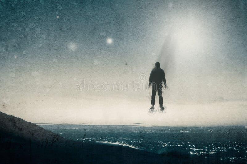 Ένας απομονωμένος με κουκούλα αριθμός που επιπλέει επάνω από έναν λόφο που κοιτάζει σε ολόκληρη μια πόλη τη νύχτα, με UFOs που επ στοκ φωτογραφίες