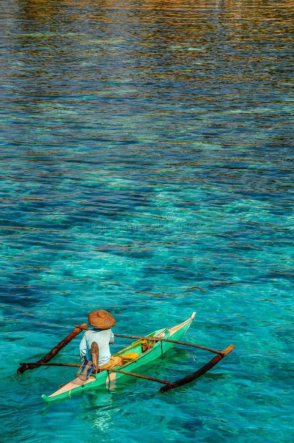 Ένας απομονωμένος ψαράς επάνω νωρίς για να πάρει την καθημερινή σύλληψή του στοκ φωτογραφία
