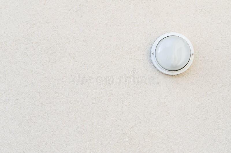 Ένας απόμερος λαμπτήρας σε έναν χλωμό κατασκευασμένο τοίχο στοκ εικόνα με δικαίωμα ελεύθερης χρήσης