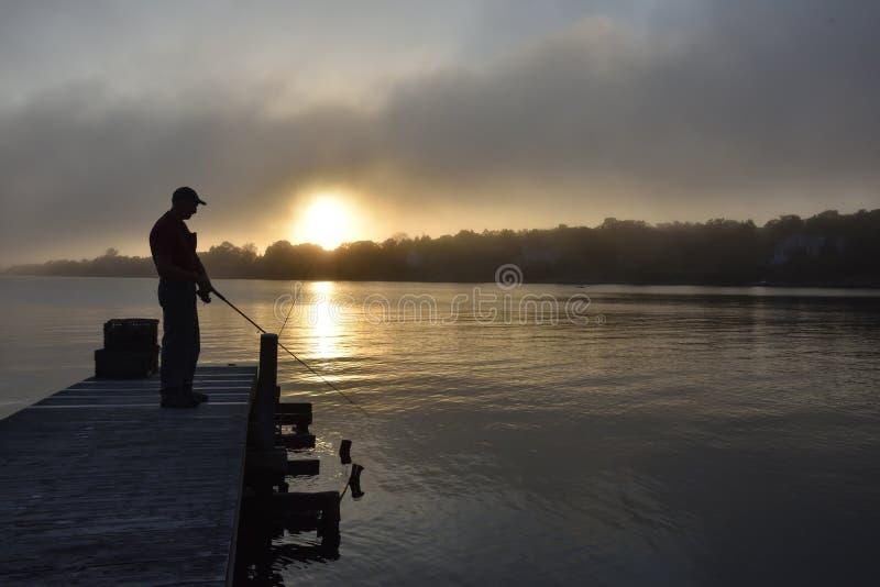 Ένας απόμερος σκιαγραφημένος αριθμός που αλιεύει από μια αποβάθρα στην ανατολή ή το ηλιοβασίλεμα στοκ εικόνες