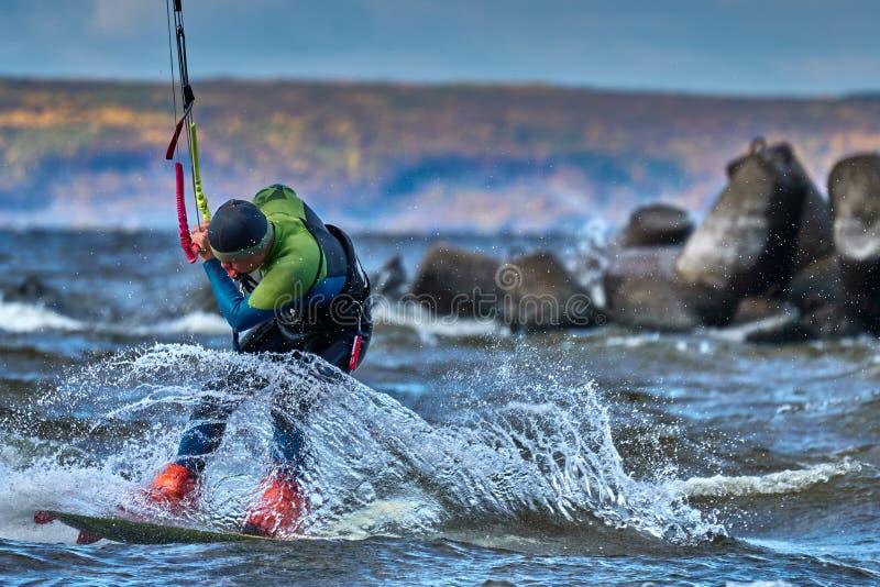 Ένας αρσενικός kiter γλιστρά στην επιφάνεια του νερού Παφλασμοί της μύγας νερού χώρια στοκ φωτογραφία με δικαίωμα ελεύθερης χρήσης