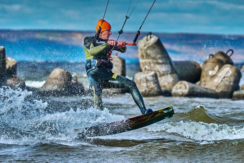 Ένας αρσενικός kiter γλιστρά στην επιφάνεια του νερού Παφλασμοί της μύγας νερού χώρια στοκ εικόνα με δικαίωμα ελεύθερης χρήσης