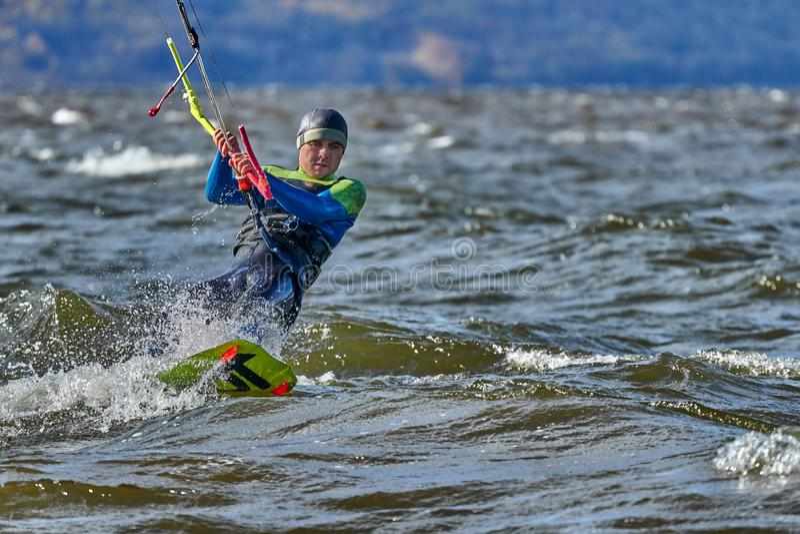 Ένας αρσενικός kiter γλιστρά στην επιφάνεια του νερού Παφλασμοί της μύγας νερού χώρια στοκ φωτογραφία