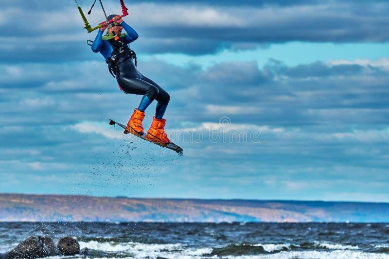 Ένας αρσενικός kiter πηδά πέρα από μια μεγάλη λίμνη Κινηματογράφηση σε πρώτο πλάνο στοκ εικόνες