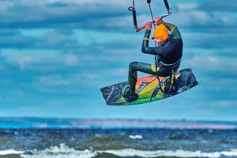 Ένας αρσενικός kiter πηδά πέρα από μια μεγάλη λίμνη Κινηματογράφηση σε πρώτο πλάνο στοκ φωτογραφίες
