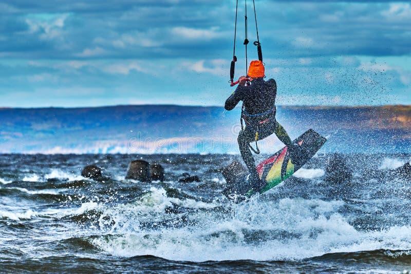 Ένας αρσενικός kiter πηδά πέρα από μια μεγάλη λίμνη Κινηματογράφηση σε πρώτο πλάνο στοκ φωτογραφία