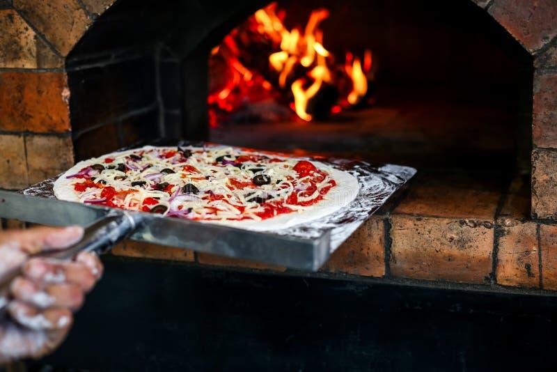 Ένας αρχιμάγειρας βάζει την εύγευστη πίτσα σε μια σόμπα για την ψημένη yummy πίτσα Διάσημα ιταλικά τρόφιμα It's στοκ φωτογραφίες