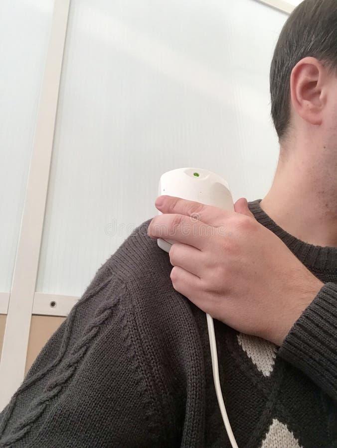 Ένας ασθενής σε ένα δωμάτιο φυσιοθεραπείας Μαγνητοθεραπεία μετά από το τραύμα Το άτομο κρατά τη συσκευή, που συνδέει την με τον ώ στοκ εικόνες με δικαίωμα ελεύθερης χρήσης