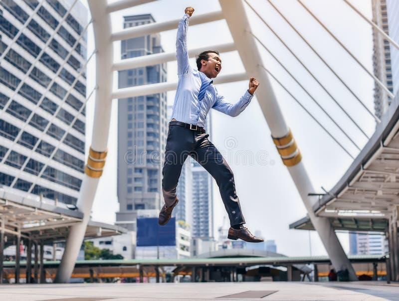 Ένας ασιατικός αρσενικός επιχειρηματίας πηδά από την επιτυχία του στο busine στοκ εικόνες