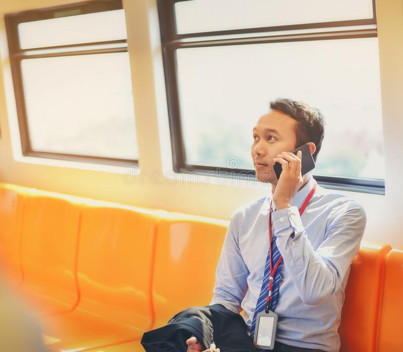 Ένας ασιατικός επιχειρηματίας ταξιδεύει ένα δημόσιο τραίνο στοκ φωτογραφίες με δικαίωμα ελεύθερης χρήσης