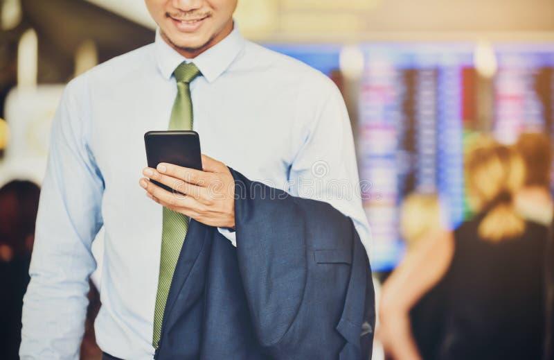 Ένας ασιατικός επιχειρηματίας χρησιμοποιεί ένα smartphone για να πάρει στην επιχείρηση wh στοκ φωτογραφίες