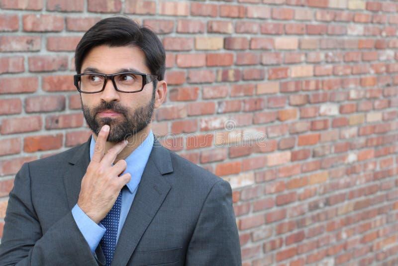 Ένας αστείος συλλογιμένος επιχειρηματίας με τα γυαλιά που κοιτάζει μακριά με το διάστημα αντιγράφων στοκ εικόνες
