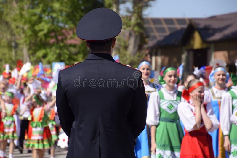 Ένας αστυνομικός, ο οποίος φωνάζει έξω την ηρεμία των πολιτών σε μια εορταστική πομπή Εορτασμός τον πρώτου του Μαΐου, η ημέρα στοκ φωτογραφία