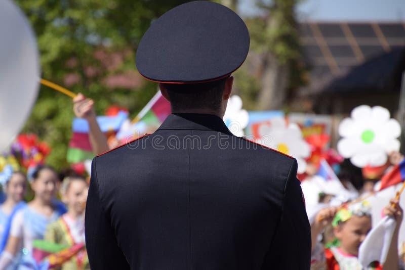 Ένας αστυνομικός, ο οποίος φωνάζει έξω την ηρεμία των πολιτών σε μια εορταστική πομπή Εορτασμός τον πρώτου του Μαΐου, η ημέρα στοκ εικόνα με δικαίωμα ελεύθερης χρήσης