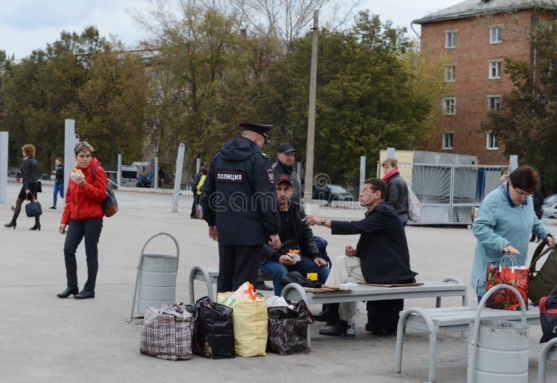 Ένας αστυνομικός προειδοποιεί τους πολίτες για την ευθύνη για το οινόπνευμα σε έναν δημόσιο χώρο στοκ εικόνες