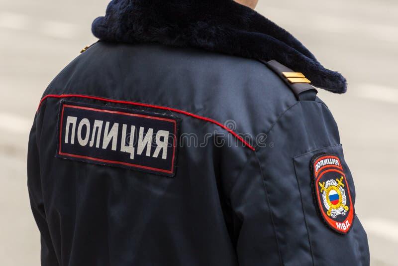 """Ένας αστυνομικός στις χειμερινές ομοιόμορφες στάσεις με την πλάτη του Αστυνομίας της επιγραφής της """"στο σακάκι στην πλάτη στοκ εικόνα με δικαίωμα ελεύθερης χρήσης"""