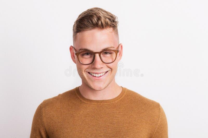 Ένας βέβαιος νεαρός άνδρας σε ένα στούντιο, που φορά τα γυαλιά στοκ εικόνα με δικαίωμα ελεύθερης χρήσης