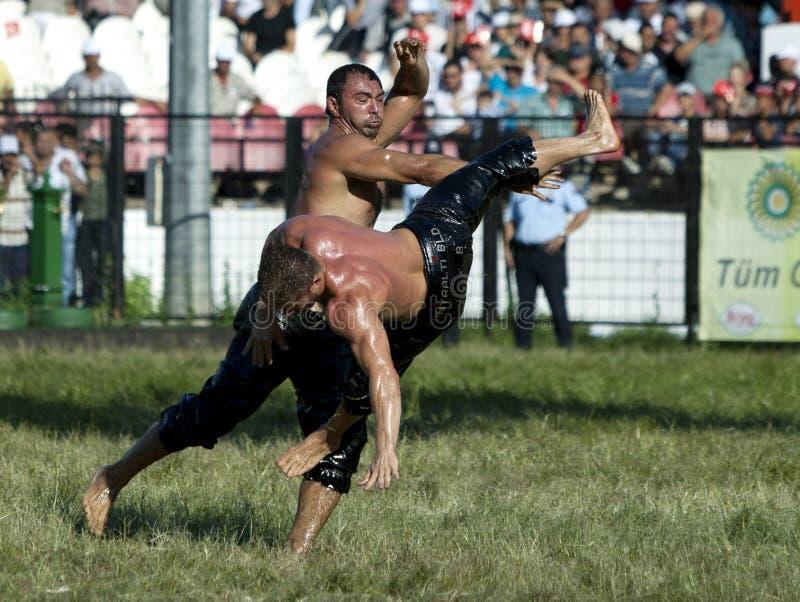 Ένας βαρέων βαρών παλαιστής πετιέται στον αέρα από τον αντίπαλό του στο τουρκικό φεστιβάλ πάλης πετρελαίου Kirkpinar στη Αδριανού στοκ εικόνες με δικαίωμα ελεύθερης χρήσης