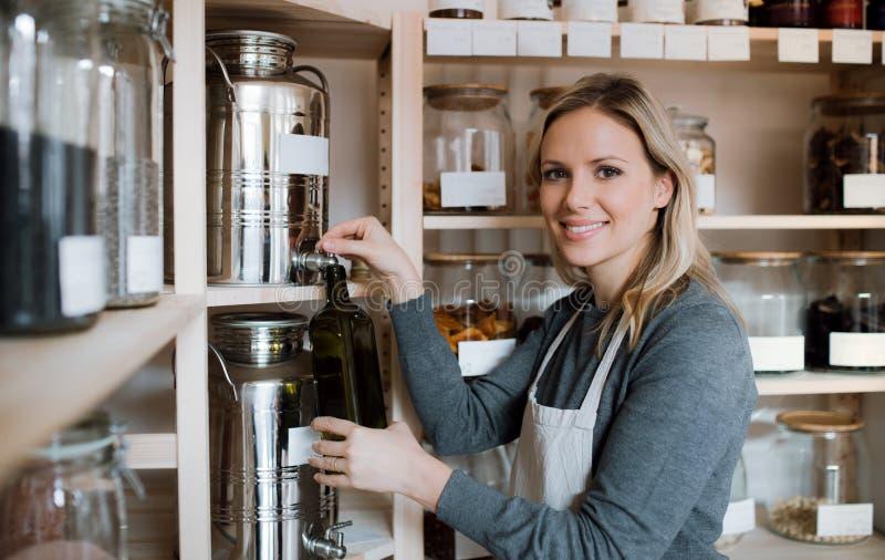 Ένας βοηθός καταστημάτων θηλυκών σε ένα μηδέν κατάστημα αποβλήτων, που γεμίζει ένα μπουκάλι με το ελαιόλαδο στοκ φωτογραφίες