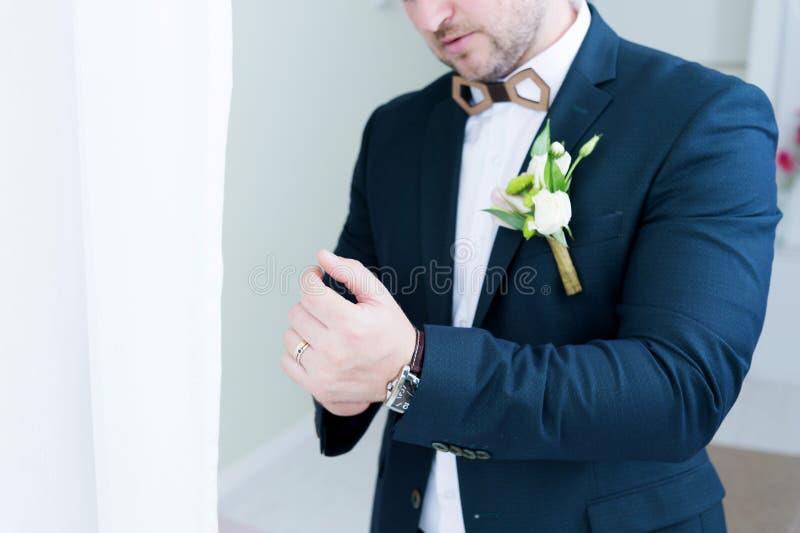 Ένας γαμπρός δυνατής μπύρας με μια γενειάδα σε ένα κοστούμι ρυθμίζει το μανίκι του σακακιού του Έξοχη κινηματογράφηση σε πρώτο πλ στοκ εικόνα με δικαίωμα ελεύθερης χρήσης