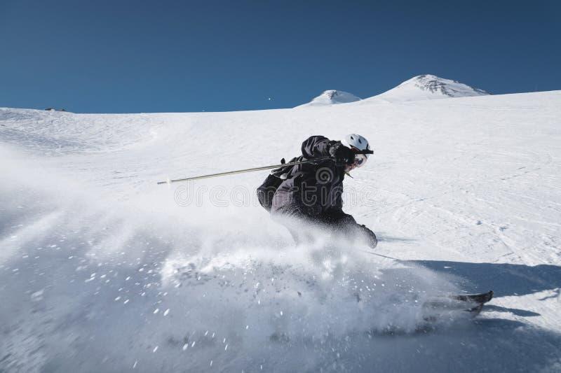 Ένας γενειοφόρος ώριμος ηλικίας αρσενικός σκιέρ σε ένα μαύρο κοστούμι σκι κατεβαίνει κατά μήκος της χιονώδους κλίσης ενός χιονοδρ στοκ εικόνες