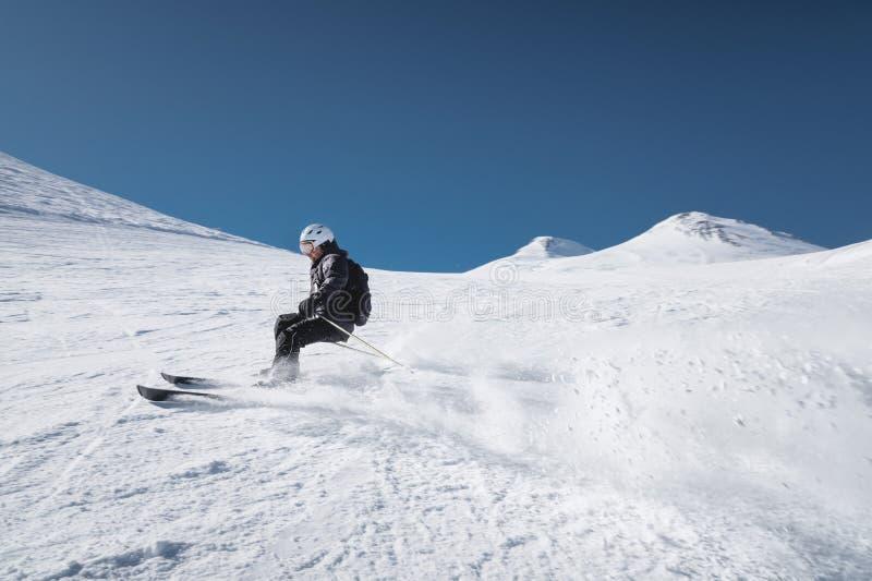 Ένας γενειοφόρος ώριμος ηλικίας αρσενικός σκιέρ σε ένα μαύρο κοστούμι σκι κατεβαίνει κατά μήκος της χιονώδους κλίσης ενός χιονοδρ στοκ φωτογραφία με δικαίωμα ελεύθερης χρήσης