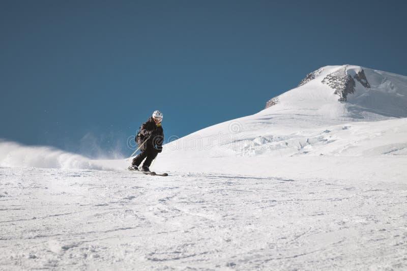 Ένας γενειοφόρος ώριμος ηλικίας αρσενικός σκιέρ σε ένα μαύρο κοστούμι σκι κατεβαίνει κατά μήκος της χιονώδους κλίσης ενός χιονοδρ στοκ εικόνα
