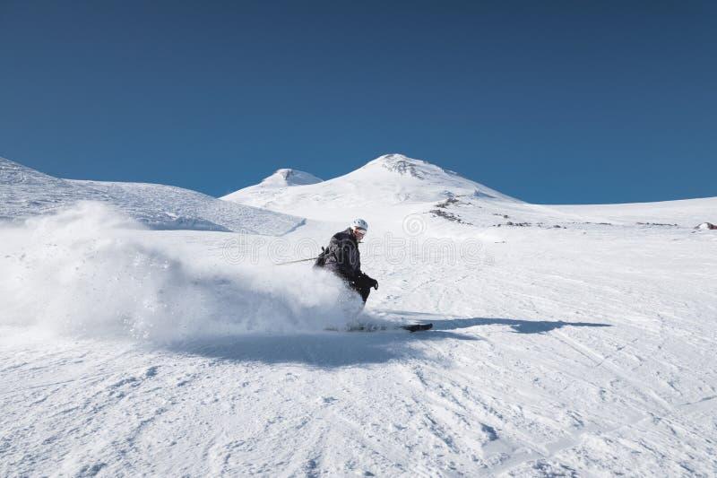 Ένας γενειοφόρος ώριμος ηλικίας αρσενικός σκιέρ σε ένα μαύρο κοστούμι σκι κατεβαίνει κατά μήκος της χιονώδους κλίσης ενός χιονοδρ στοκ φωτογραφίες