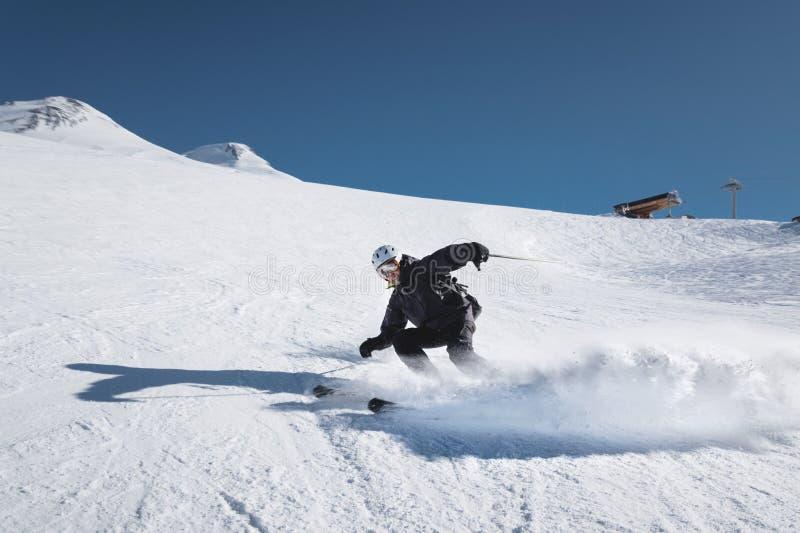 Ένας γενειοφόρος ώριμος ηλικίας αρσενικός σκιέρ σε ένα μαύρο κοστούμι σκι κατεβαίνει κατά μήκος της χιονώδους κλίσης ενός χιονοδρ στοκ φωτογραφία