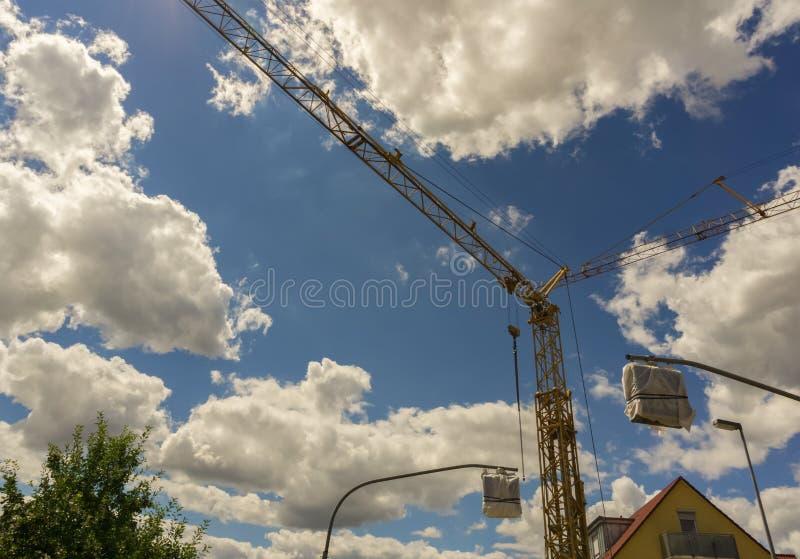 Ένας γερανός σε Herrenberg κάτω από έναν νεφελώδη θερινό ουρανό στοκ φωτογραφίες