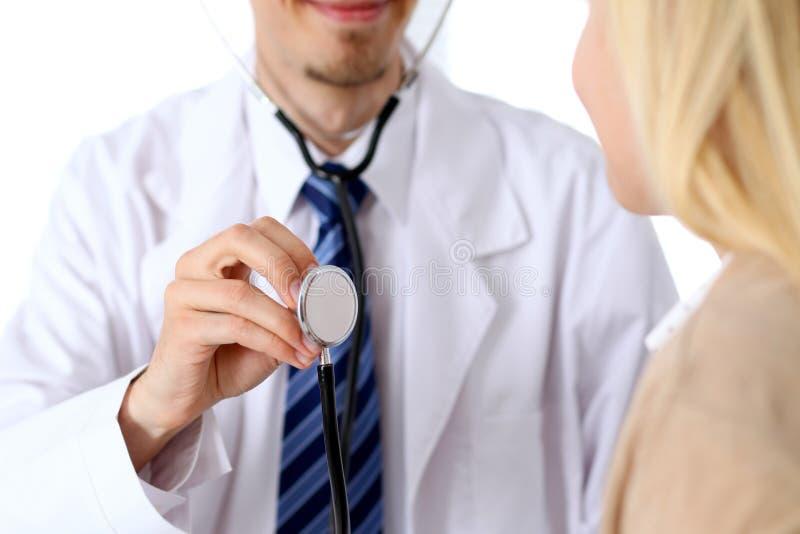 Ένας γιατρός με ένα στηθοσκόπιο στο χέρι του δίπλα στον ασθενή του Ο θεράπων είναι έτοιμος να εξετάσει έναν ασθενή στοκ φωτογραφία με δικαίωμα ελεύθερης χρήσης