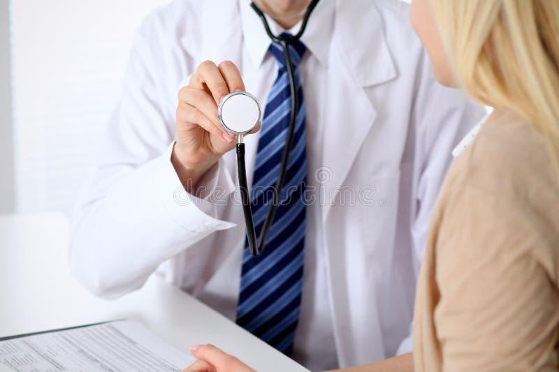 Ένας γιατρός με ένα στηθοσκόπιο στο χέρι του δίπλα στον ασθενή του Ο θεράπων είναι έτοιμος να εξετάσει έναν ασθενή στοκ εικόνα