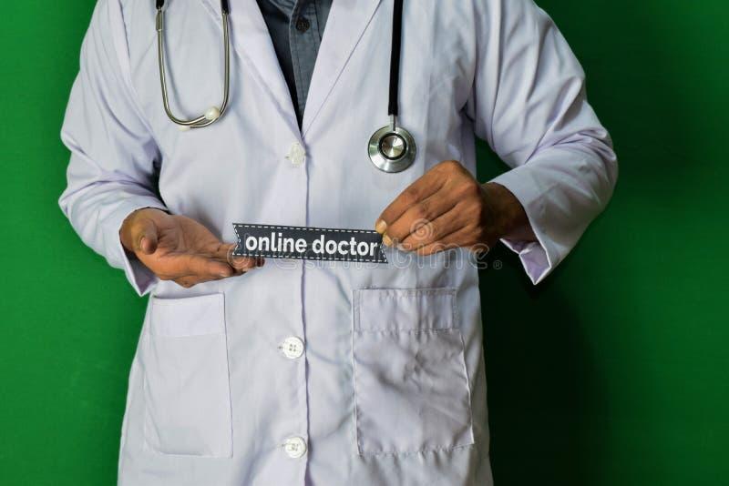 Ένας γιατρός που στέκεται, κρατά το σε απευθείας σύνδεση κείμενο εγγράφου γιατρών στο πράσινο υπόβαθρο Ιατρική και έννοια υγειονο στοκ εικόνες