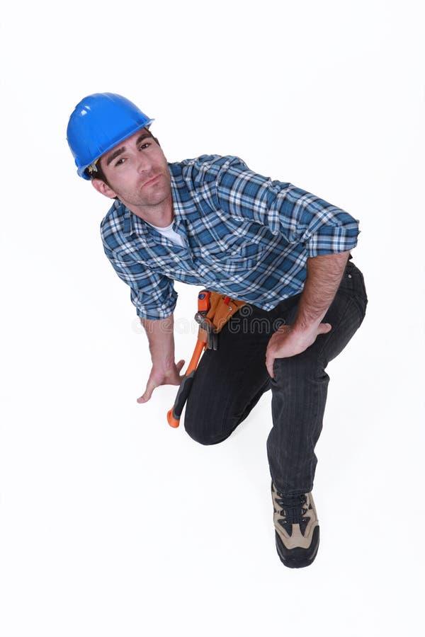 Ένας γονατισμένος εργάτης οικοδομών. στοκ φωτογραφία