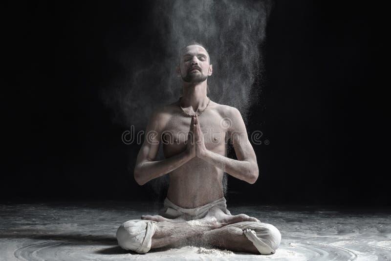 Ένας δάσκαλος γιόγκας κάθεται σε ένα sukhasana σε ένα μαύρο υπόβαθρο στοκ φωτογραφία με δικαίωμα ελεύθερης χρήσης