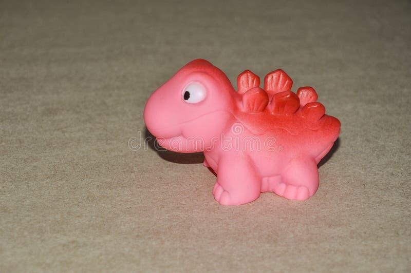 Ένας δεινόσαυρος παιχνιδιών ροζ παιχνιδιών παιδιών στοκ εικόνες με δικαίωμα ελεύθερης χρήσης
