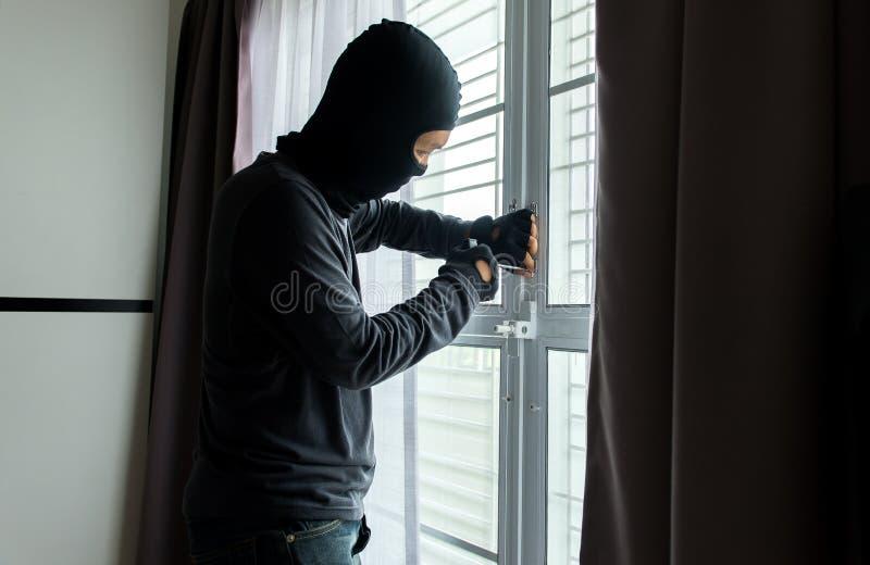 Ένας διαρρήκτης ατόμων στη μαύρη μάσκα ανοίγει την πόρτα κλέβοντας κάτι από το σπίτι στοκ φωτογραφία με δικαίωμα ελεύθερης χρήσης